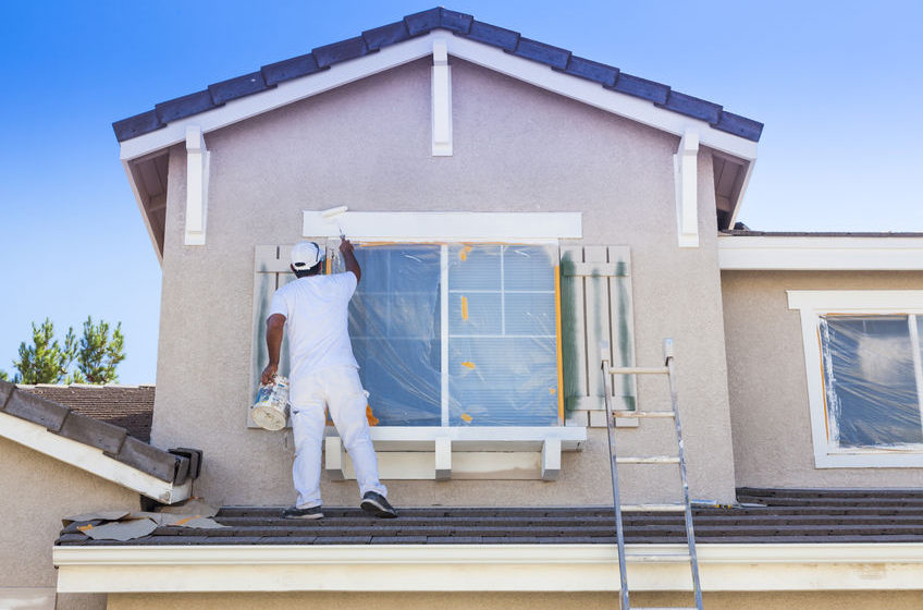 35162804 - busy house painter painting the trim and shutters of a home.